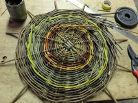 Base for my large bread basket. The bright orangey yellow is fresh (undried) willow and will turn red as it dries. It will also shrink a bit so we used it very sparingly and had to be sure to weave it tight and close.. The yellow outer ring will dry to a paler yellow.
