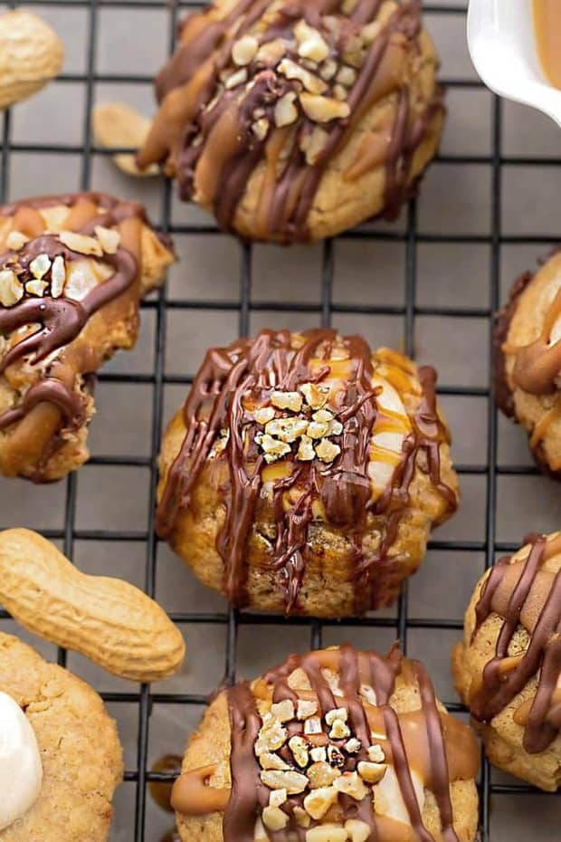 Snickers Thumbprint Cookies are the perfect homemade treat to add to any holiday cookie tray. Soft & chewy peanut butter cookies topped with marshmallow nougat filling drizzled with melted chocolate and caramel.