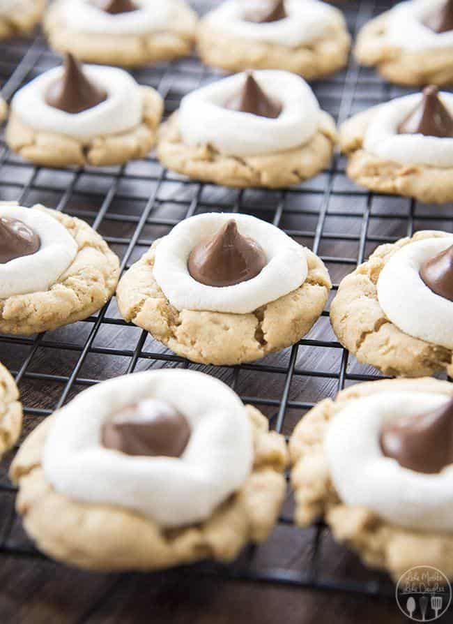 S'mores Cookies start with a graham cracker filled cookie base, topped with a gooey marshmallow, and a chocolate kiss - for your favorite s'mores flavors in a delicious and cute cookie!