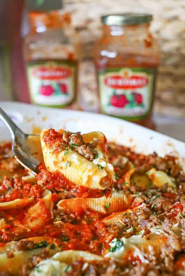 Loaded with spinach, garlic, sausage, ricotta & smothered in marinara sauce, these Stuffed Shells make a great easy family dinner idea that everyone loves.