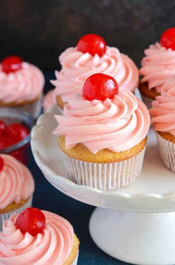 Perfect sweet vanilla and almond scented cupcakes are filled with bites of red maraschino cherries and topped with a gorgeous bright pink maraschino cherry frosting.