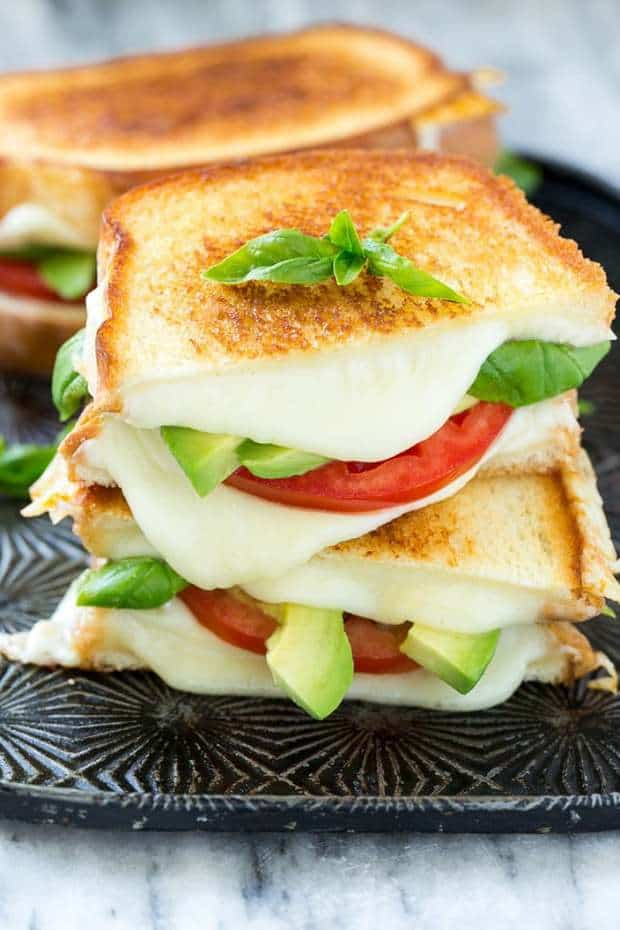 Caprese Sandwich Recipe is the classic combination of tomatoes, mozzarella and basil with the welcome addition of avocado slices, all sandwiched together between slices of buttery toasted bread.