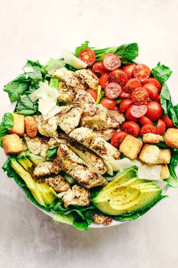 Grilled Chicken Caesar Avocado Saladis a mouthwatering classic salad with juicy grilled chicken, crisp romaine lettuce, cherry tomatoes, avocado, and topped with shaved mozzarella and crunchy croutons!
