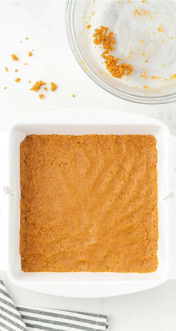Pressing graham cracker mixture evenly into the bottom of the pan