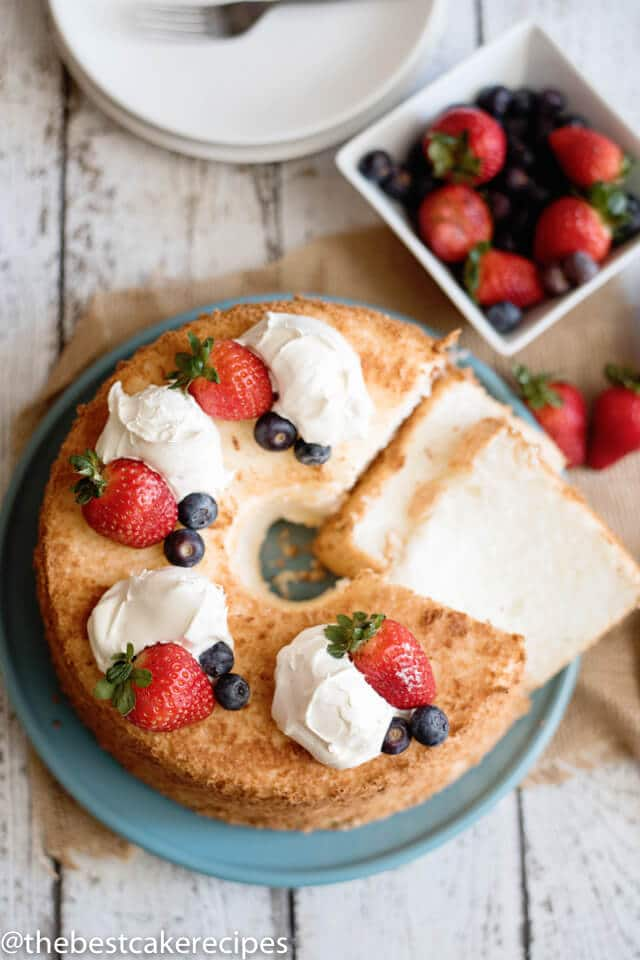 overhead view of an angel food cake with fresh berries and cream