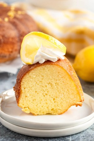 lemon pound cake on a plate with whipped cream and lemon