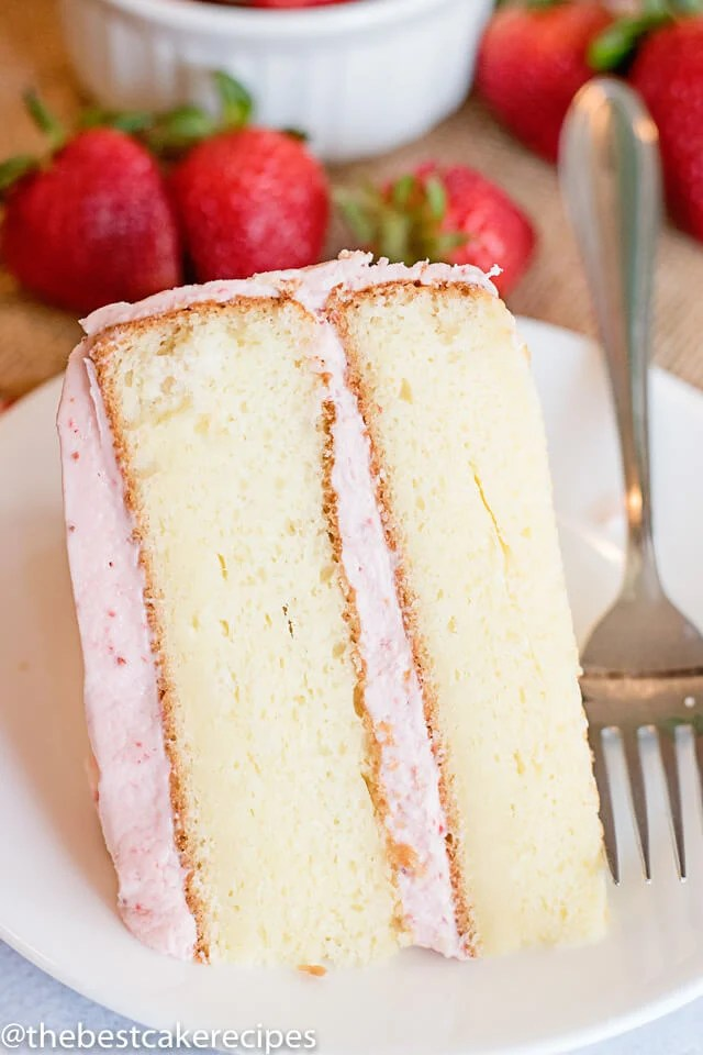 easy white cake with strawberry buttercream on a plate with a fork