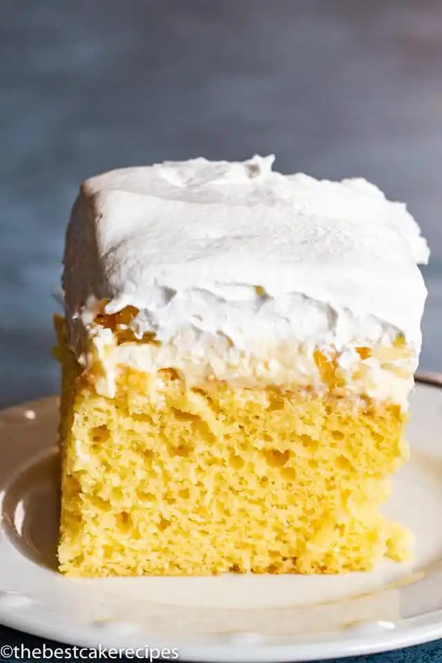 Pineapple Cream Cake with cream cheese and whipped cream on a plate