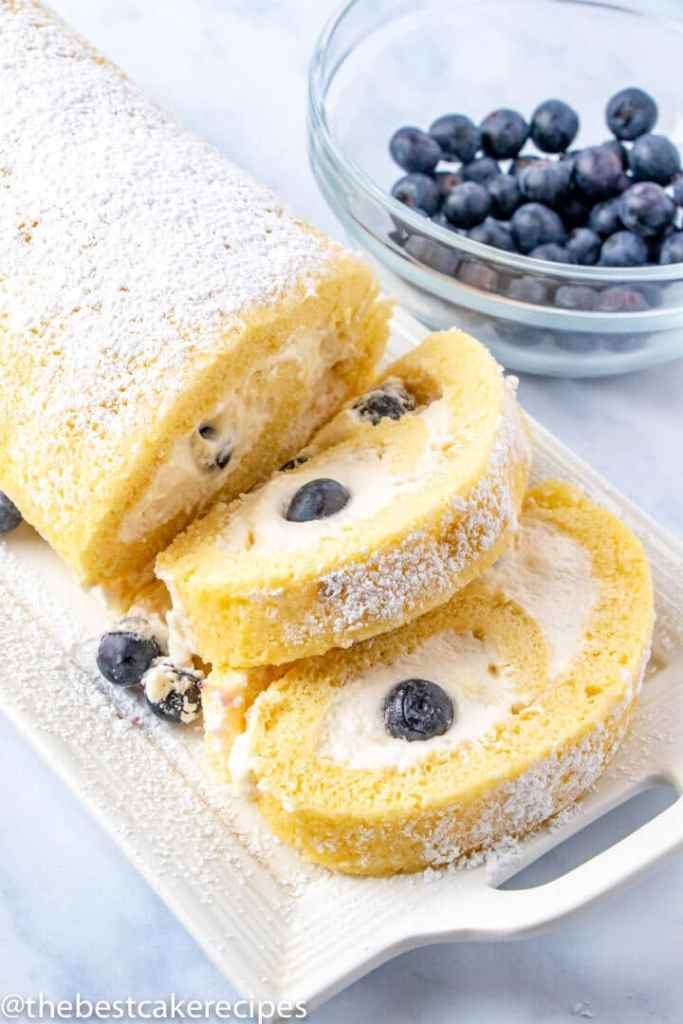 sliced yellow cake roll with blueberries