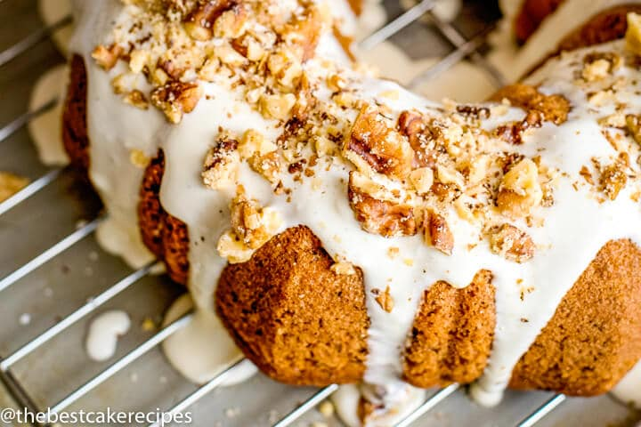 Easy Banana Bundt Cake Recipe with Cream Cheese Glaze and Walnuts on a wire rack
