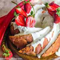 Strawberry Rhubarb Bundt Cake with glaze and strawberries on a plate
