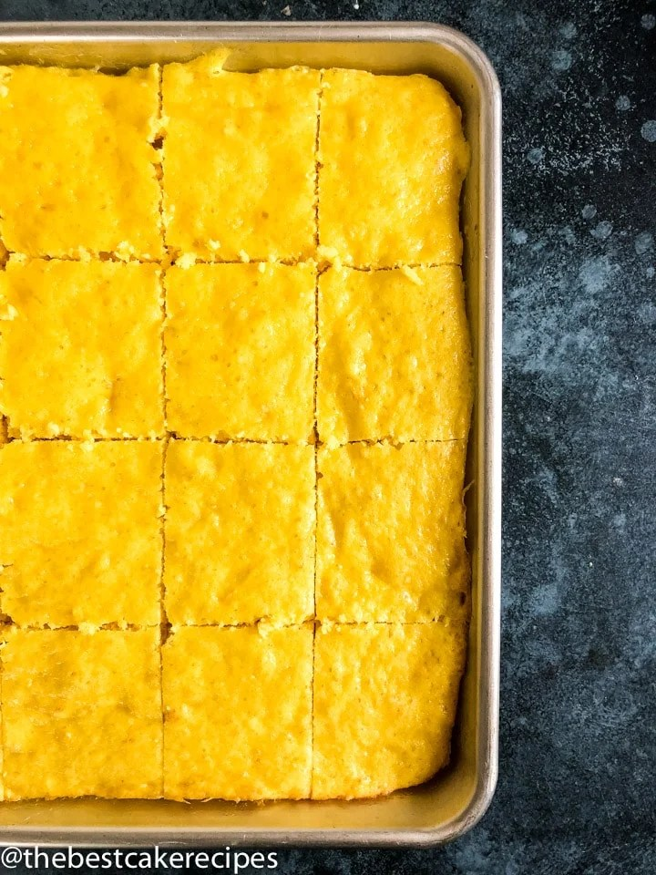 unfrosted lemon cake sliced in a baking pan