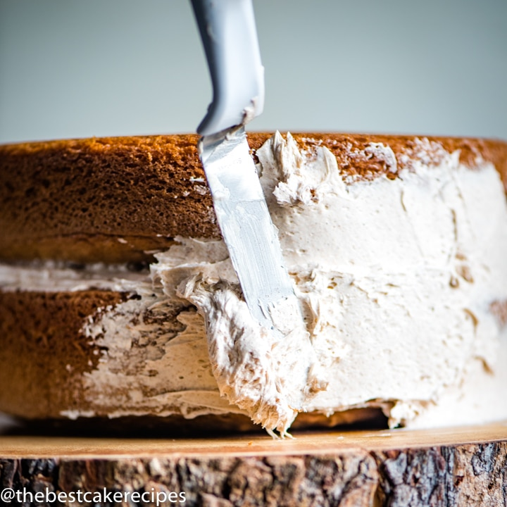 frosting a Cinnamon Layer Cake Recipe with a spatula