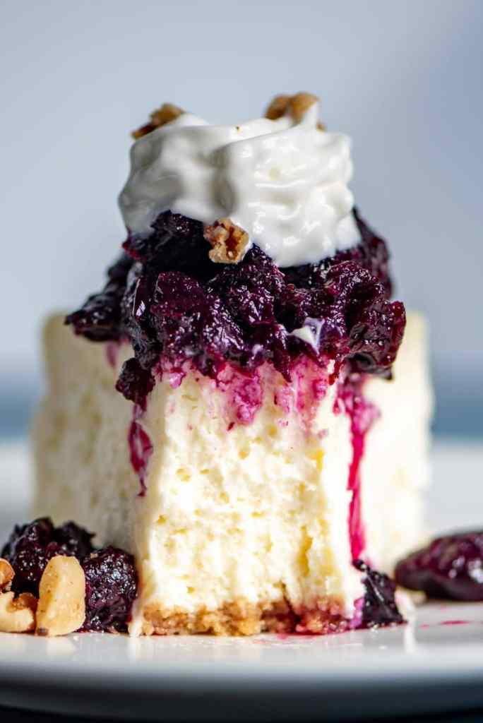 white cheesecake with blueberry topping on a plate