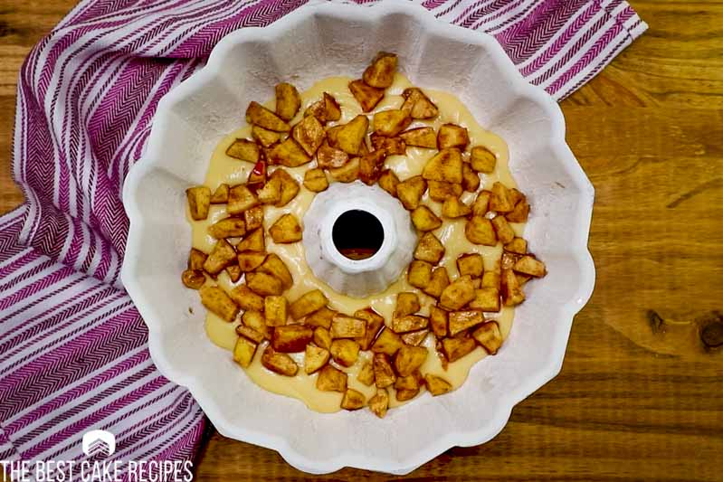 cake batter and cinnamon apples in a bundt cake pan