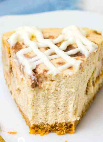 Cinnamon Roll Cheesecake on a plate with a bite out