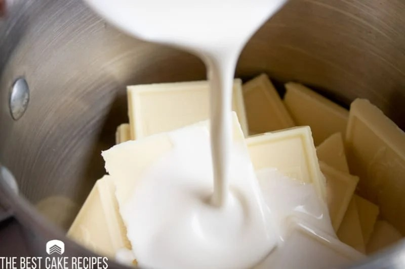 heavy cream pouring into a bowl of white chocolate