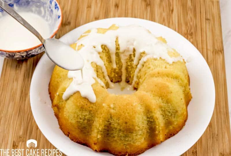 spooning frosting on a bundt cake