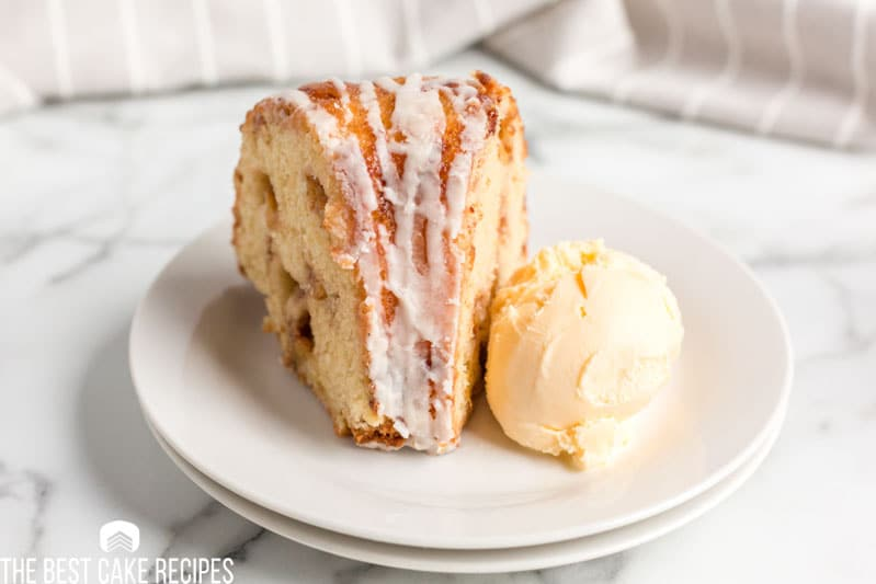 peach swirl bundt cake on a plate with ice cream on the side