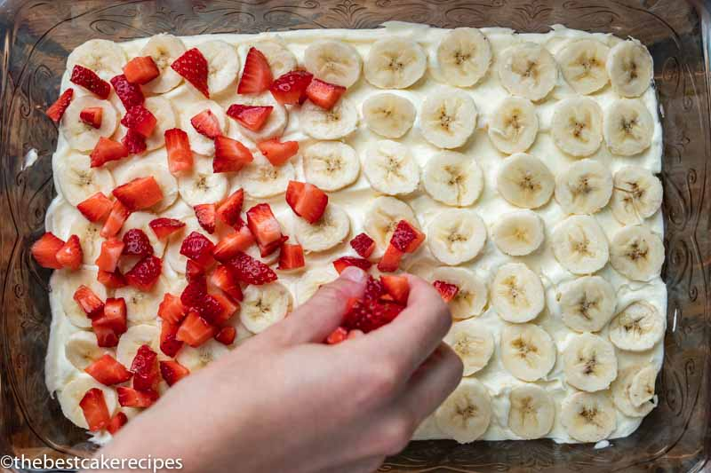 placing strawberries and bananas on a cake