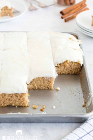 buttermilk sheet cake in a pan with several pieces missing