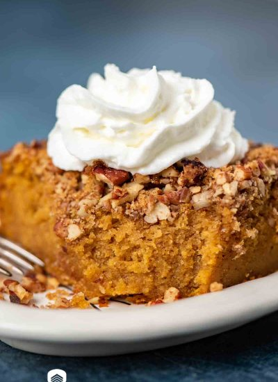 slice of pumpkin cake on a plate with a dollop of whipped cream