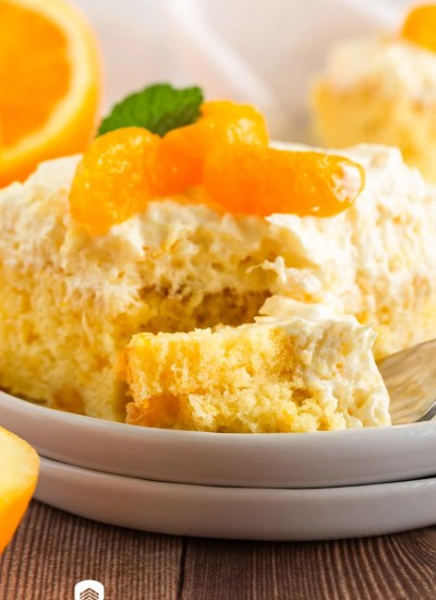 piece of mandarin orange cake on a plate with a bite on a fork
