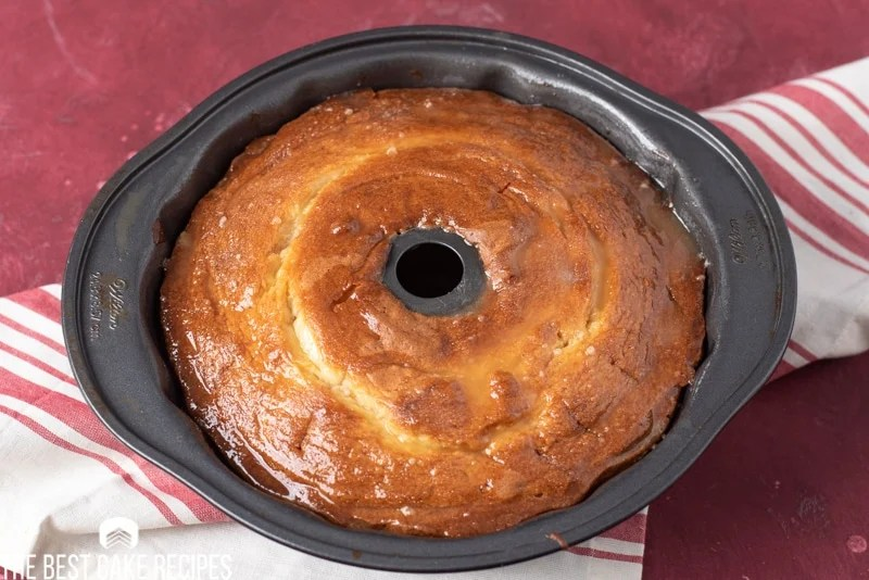 pound cake in pan with glaze
