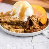 plate of peach dump cake with ice cream
