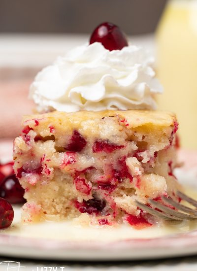 piece of cranberry pudding cake with whipped topping on a plate