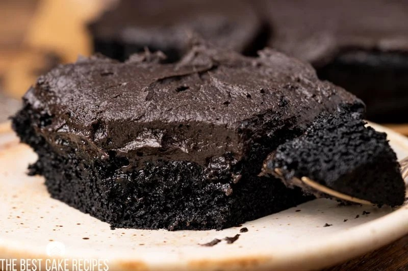 a piece of fudgy chocolate cake on a plate with a fork