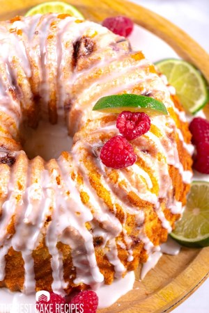 overhead view of a bundt cake with limes and raspberries