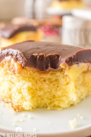 a piece of boston cream poke cake with a bite out