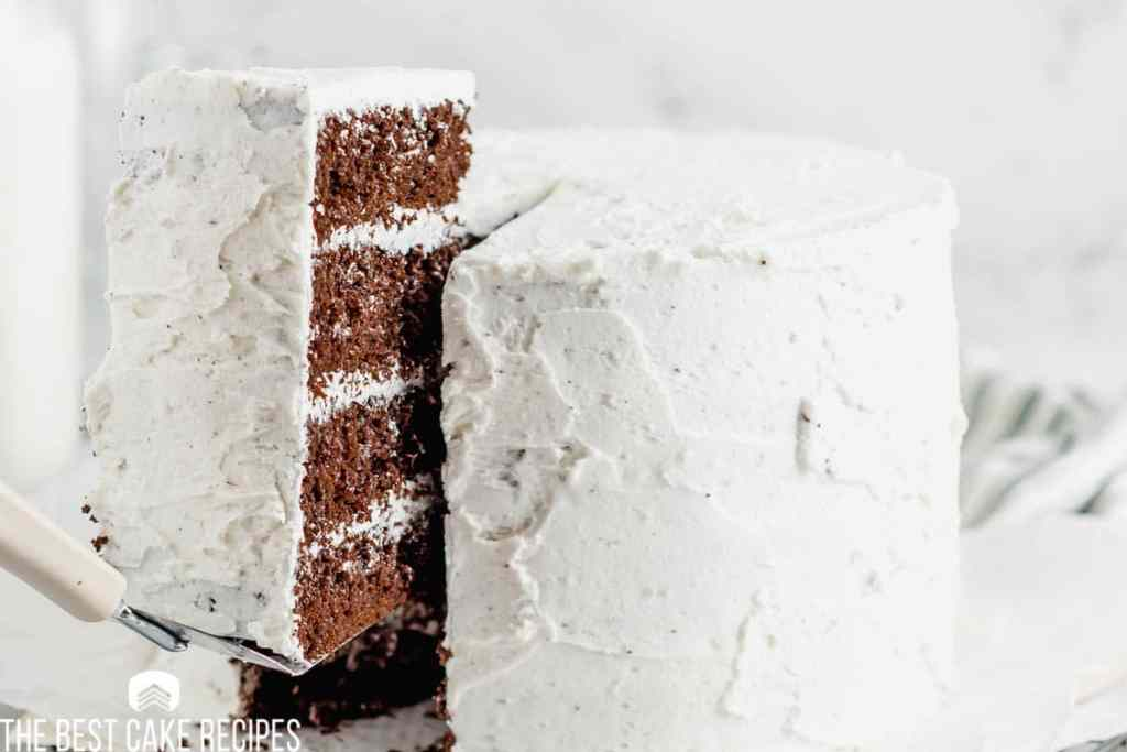 a piece of chocolate cake with white frosting on a spatula