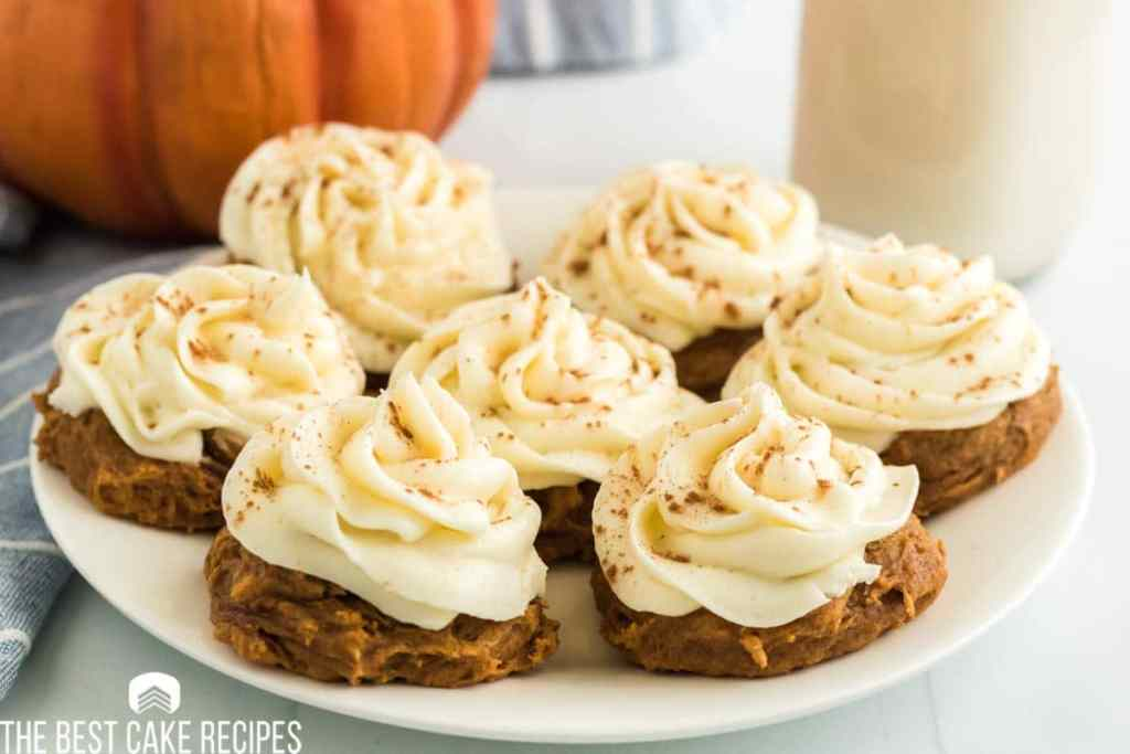 a plate of frosted pumpkin cookies