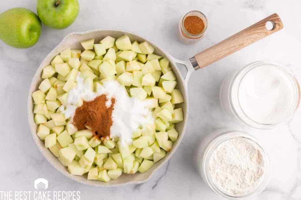 chopped apples in a skillet with sugar and cinnamon