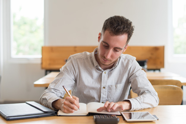 Young man writing on a book