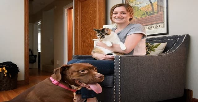 Christine Hinrichs with her rescue pets, pit bull mix Olive, 5, and one of her cats, Ruby, 7. Hinrichs is a volunteer for Pet Project Rescue.
