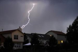 A lightning bolt strikes behind a few houses.