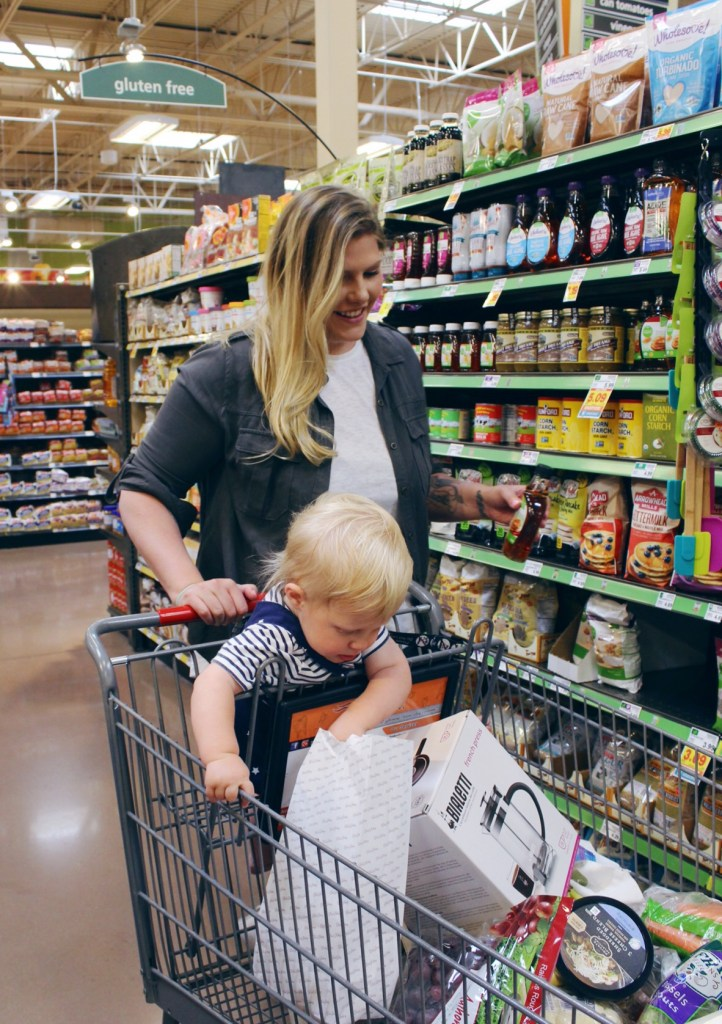 mom shopping in the grocery store with child and groceries in cart