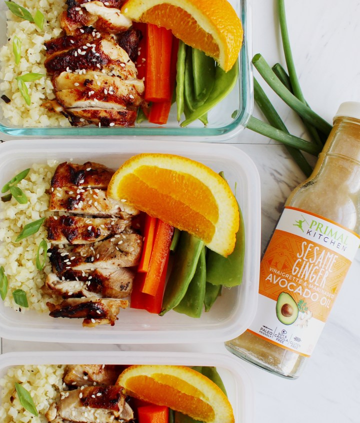 chicken meal prep bowls with bottle of marinade