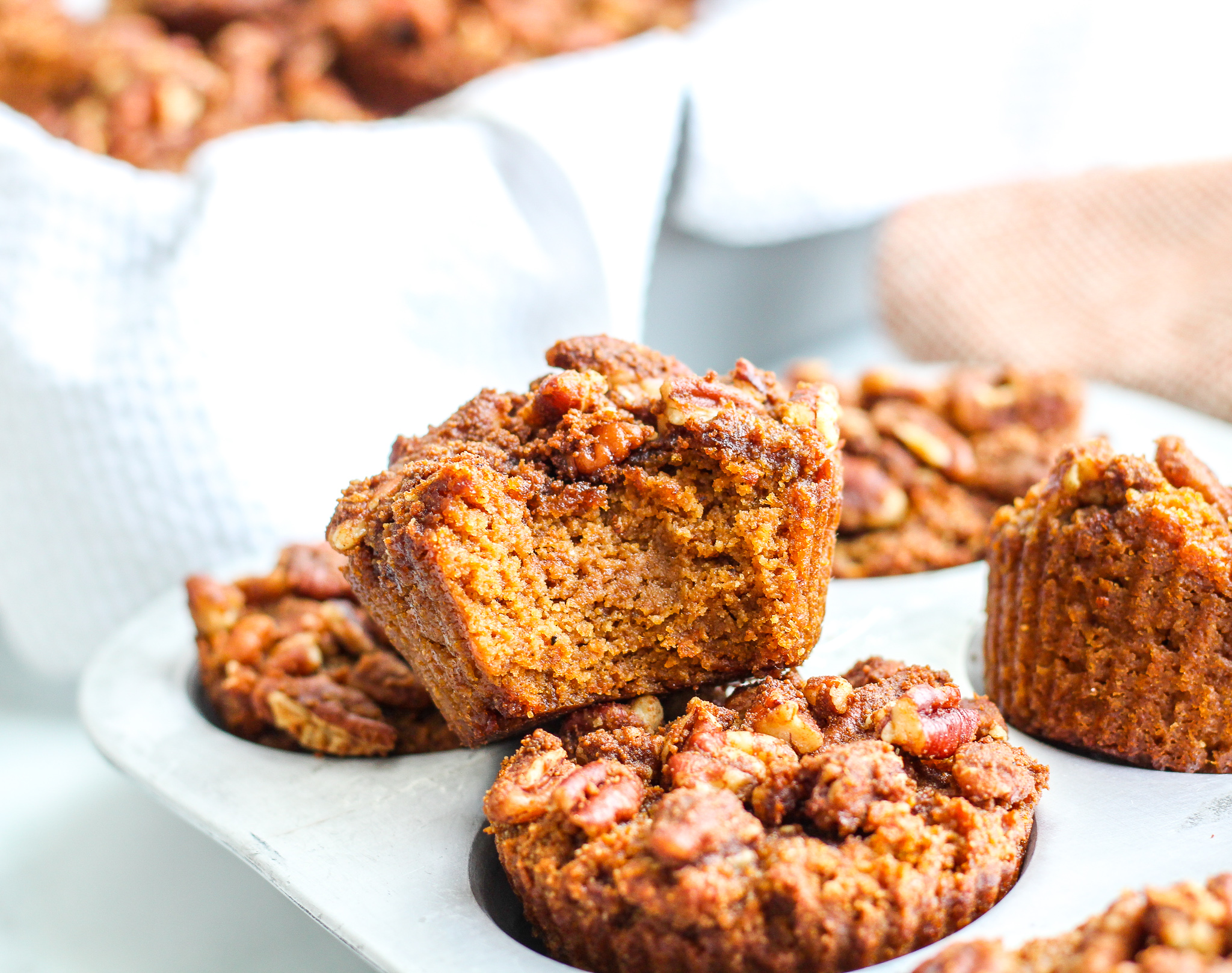 Paleo Pumpkin Streusel Muffin with a bite taken out of it sitting on top of a silver muffin tin