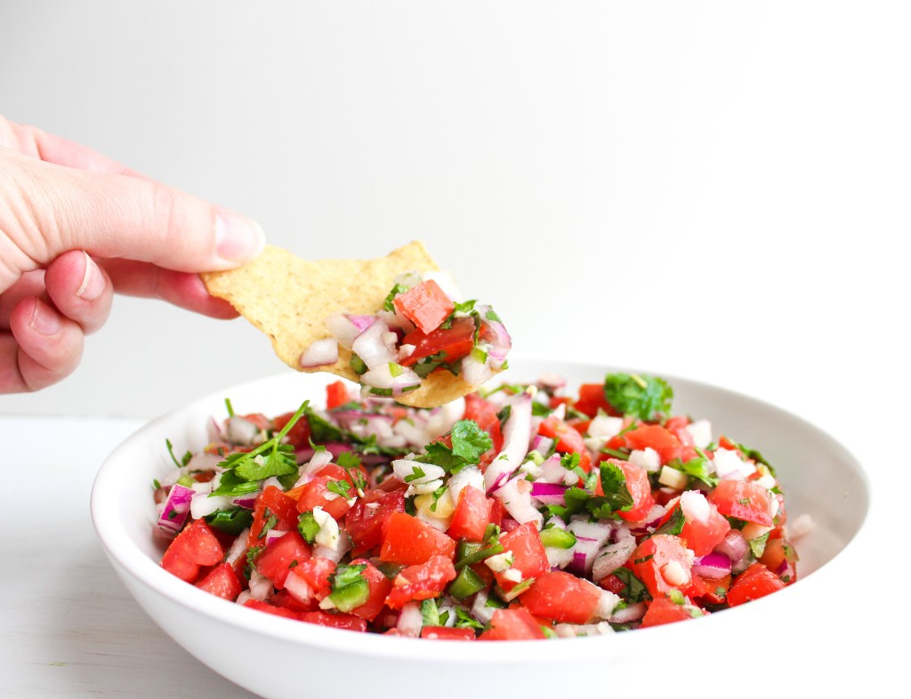 Hand holding tortilla chip dipped in pico de Gallo