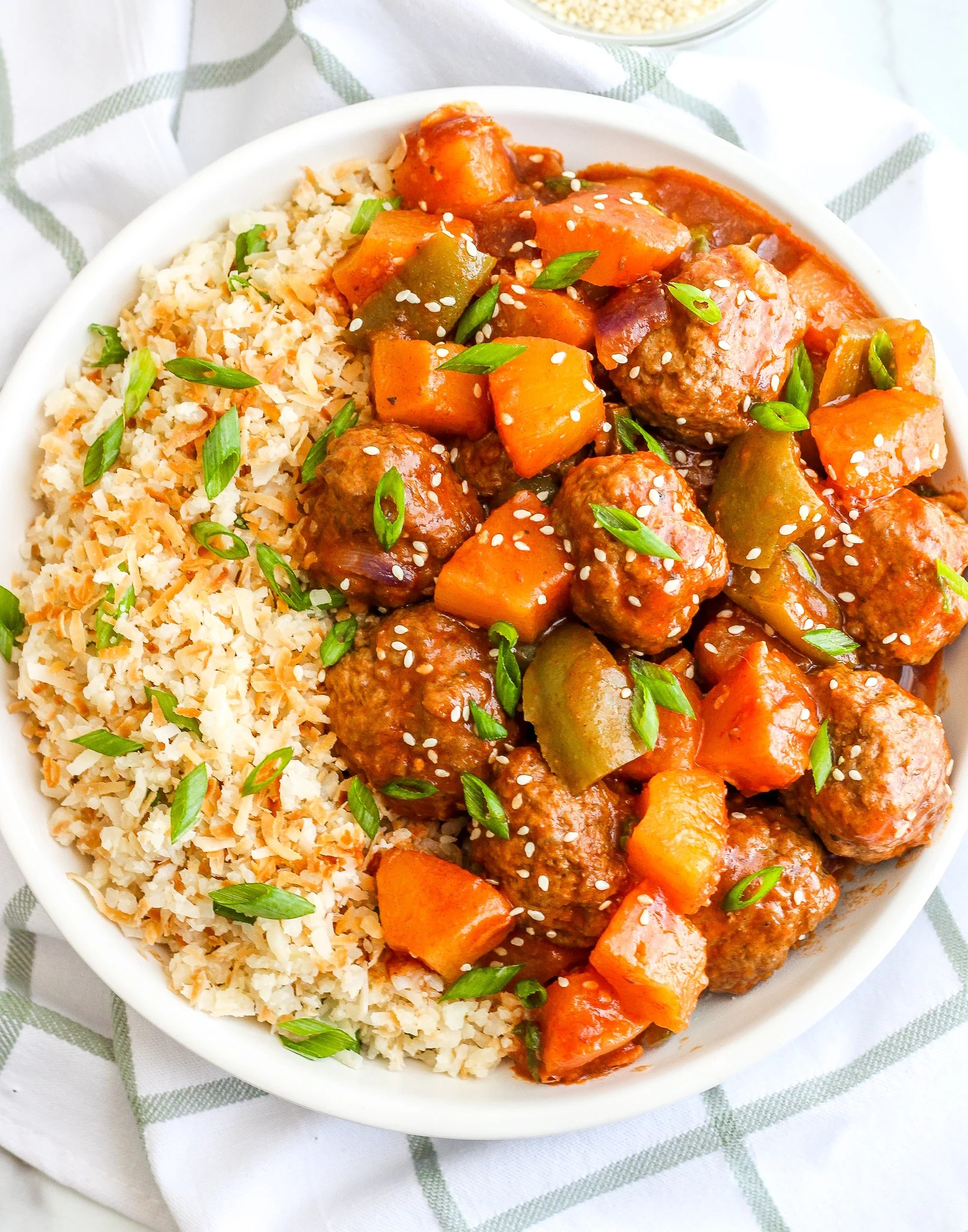 Sweet & Sour Meatballs with Coconut Cauliflower Rice in a white serving bowl, topped with green onions and sesame seeds