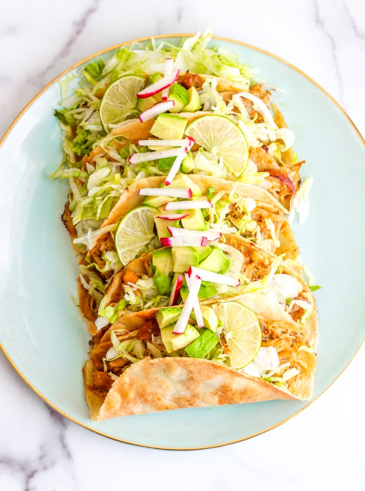 Overhead shot of baked chicken tacos loaded up with avocado, limes, radishes and shredded lettuce
