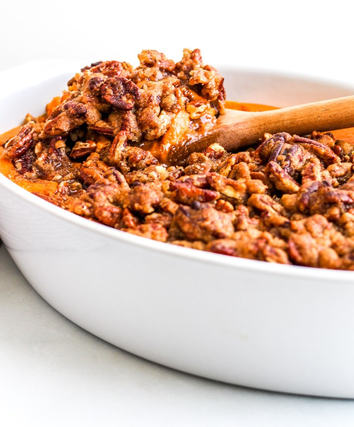 Sweet Potato Casserole topped with a pecan topping, a spoon is scooping some out of a white dish