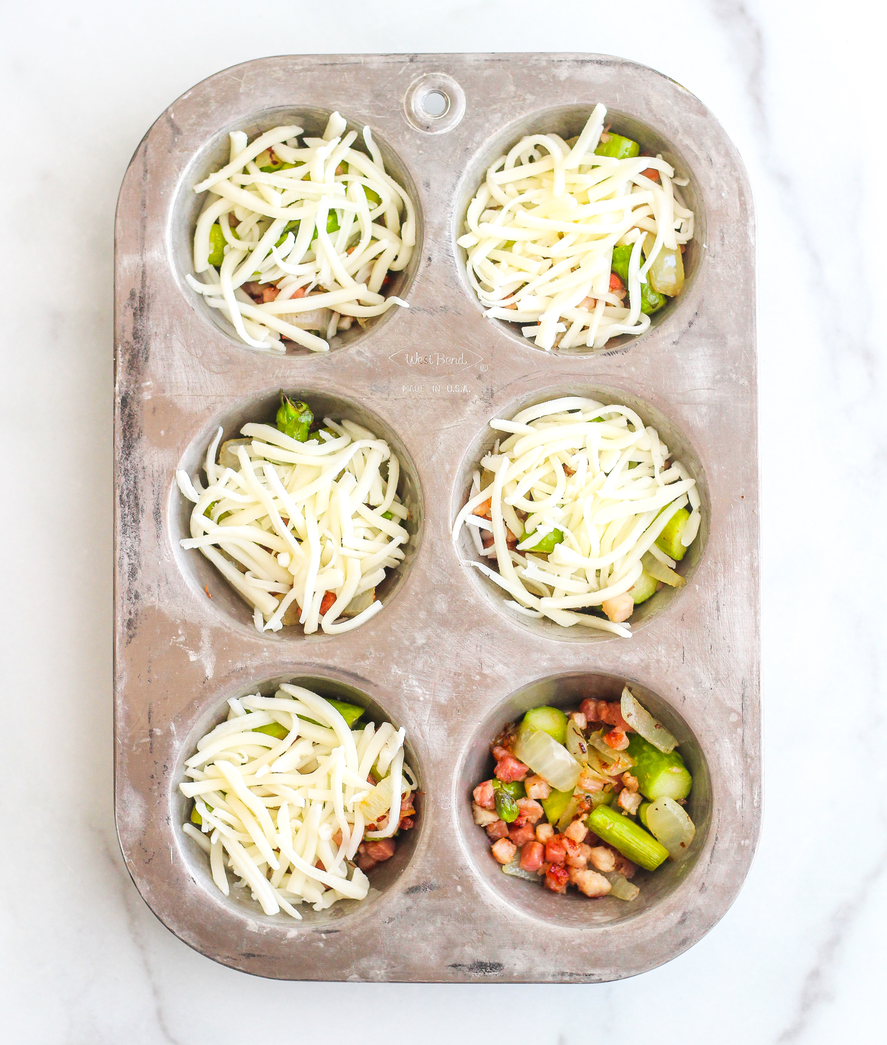 silver muffin tin filled with pancetta and asparagus topped with shredded cheese