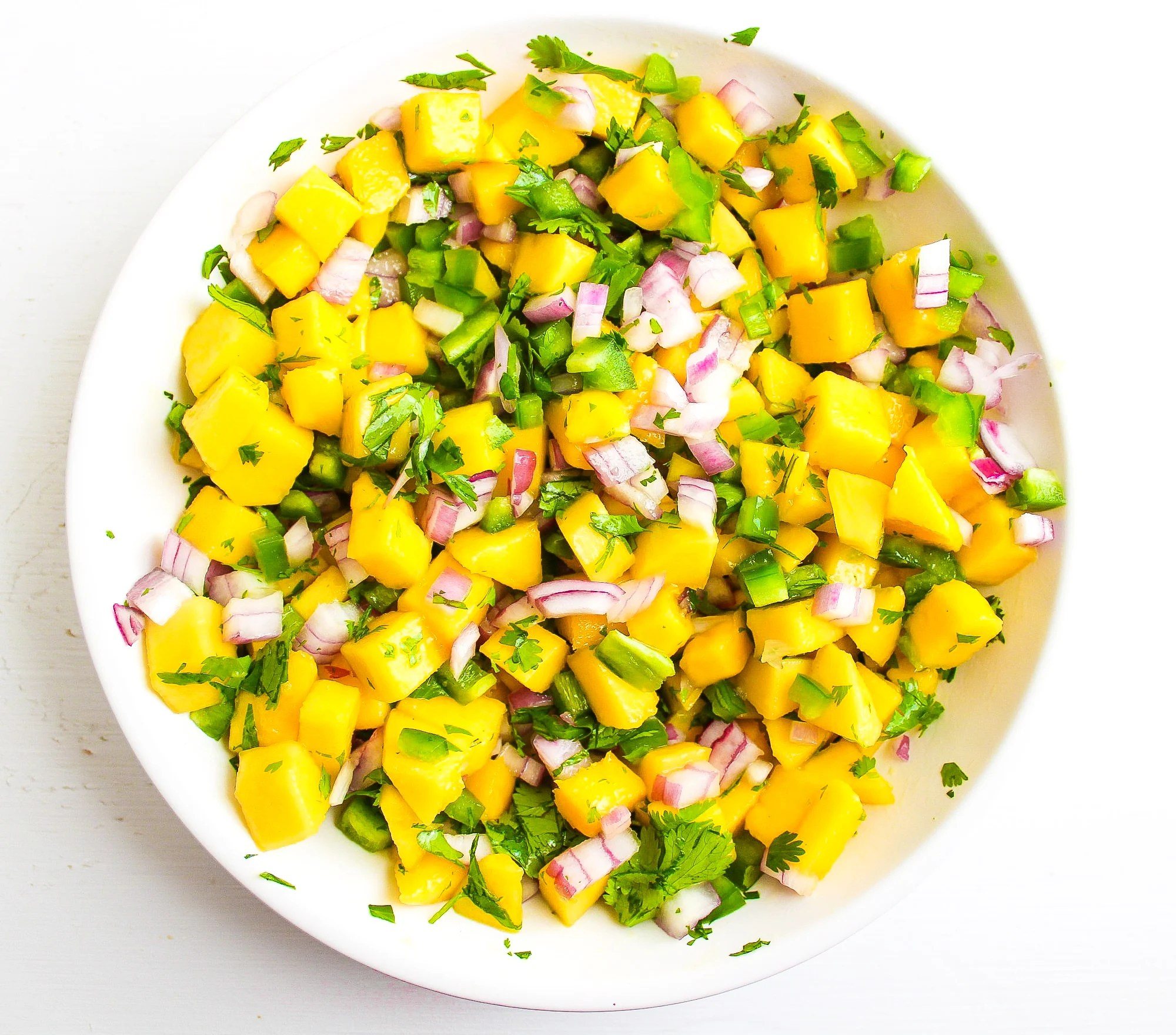 White bowl filled with fresh mango salsa