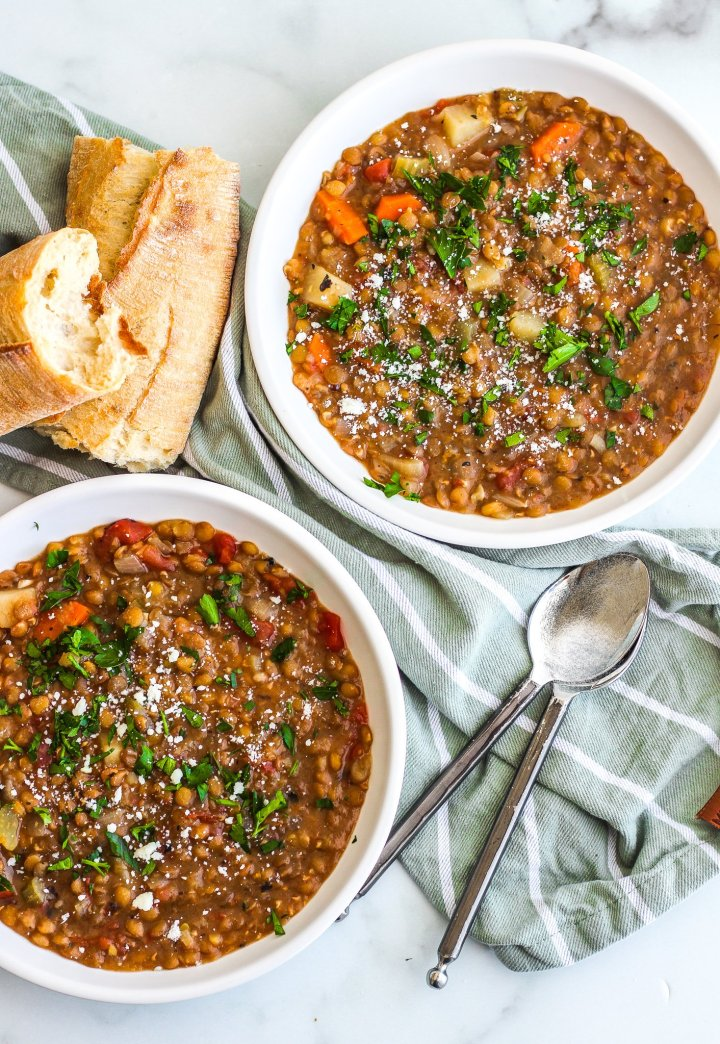 Instant Pot lentil stew in two white bowls with spoons on the side and torn bread loaves
