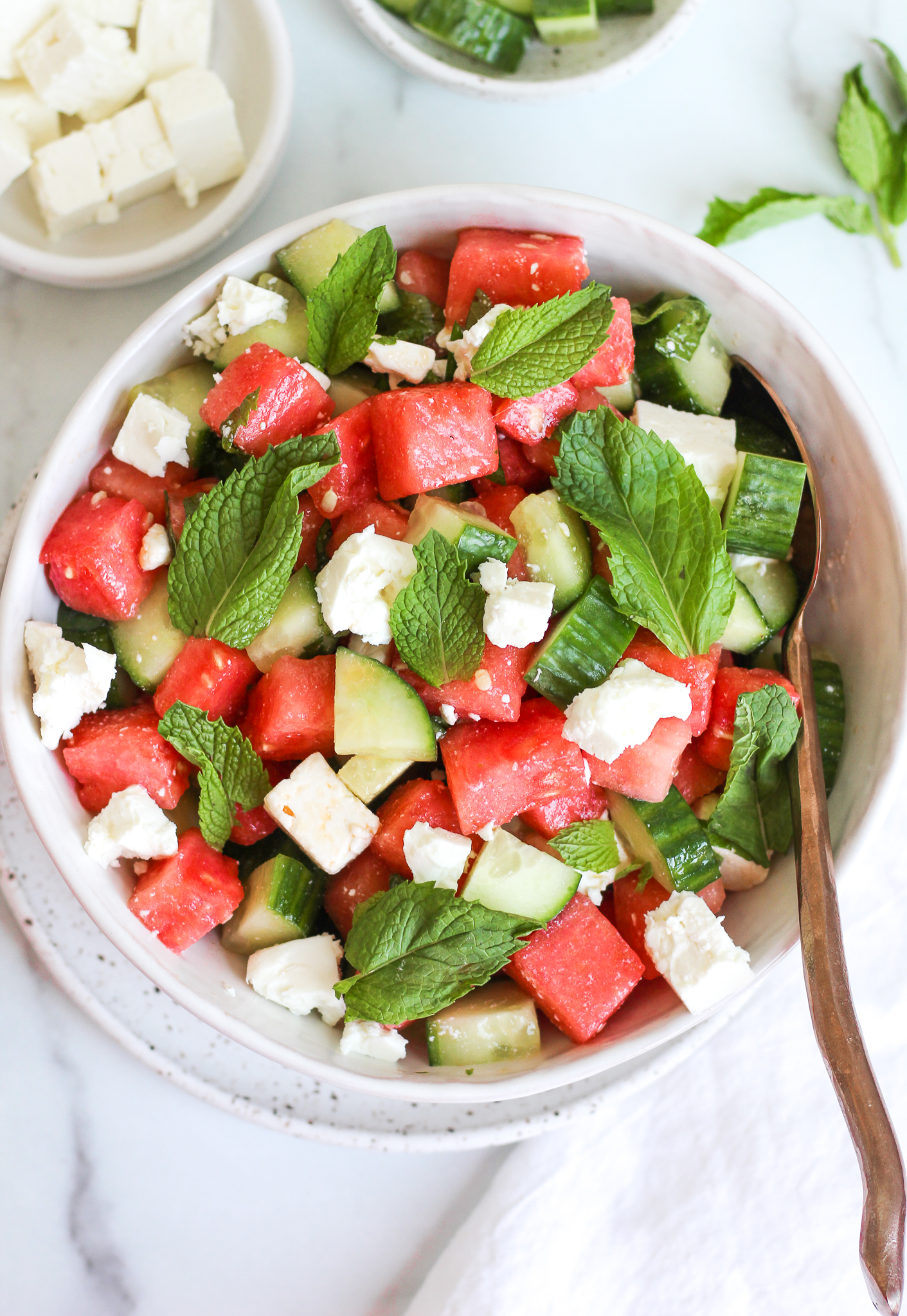Watermelon cucumber salad in a white ceramic mixing bowl topped with fresh mint and feta cheese